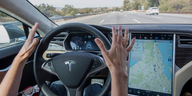 """A member of the media test drives a Tesla Motors Inc. Model S car equipped with Autopilot in Palo Alto, California, U.S., on Wednesday, Oct. 14, 2015. Tesla Motors Inc. will begin rolling out the first version of its highly anticipated """"autopilot"""" features to owners of its all-electric Model S sedan Thursday. Autopilot is a step toward the vision of autonomous or self-driving cars, and includes features like automatic lane changing and the ability of the Model S to parallel park for you. Photographer: David Paul Morris/Bloomberg via Getty Images"""